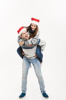 クリスマスのコンセプト-白い灰色の壁に隔離されたピギーバックライドを楽しんでセーターのフルレングスの若い幸せなカップル。