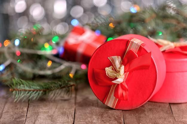 クリスマスのコンセプト。木製のテーブルとぼやけた背景のギフトボックスと装飾