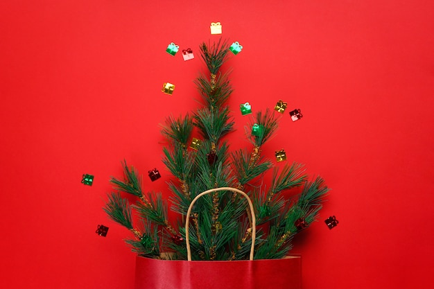 Christmas concept. green spruce branches in a package of red paper on red with confetti. flat lay.