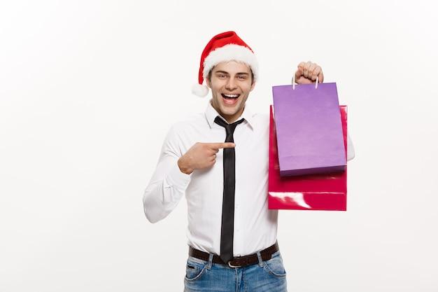 Концепция рождества - красивый бизнесмен празднует счастливого рождества и счастливого нового года в шляпе санта-клауса с сумкой для покупок.