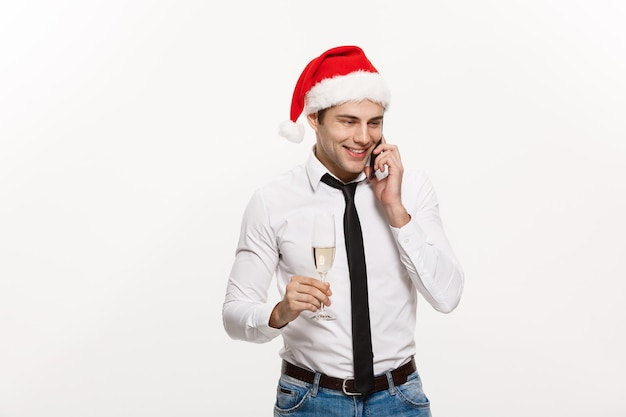 クリスマスのコンセプト-ハンサムなビジネスマンが電話で話し、chirstmasと新年を祝うシャンパングラスを持っています。