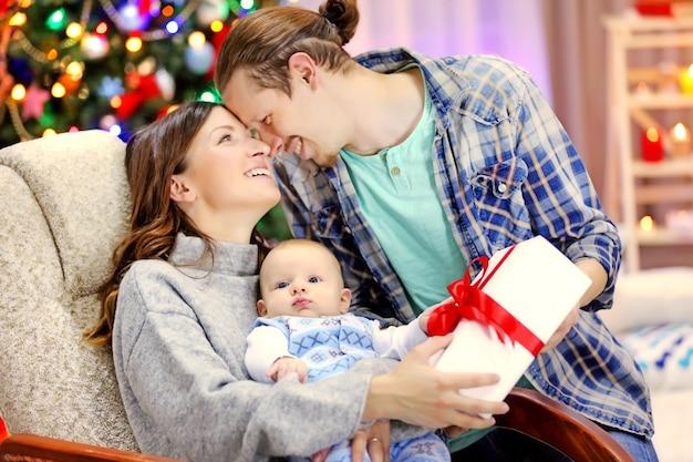 クリスマスのコンセプト:装飾された部屋で幸せな家族