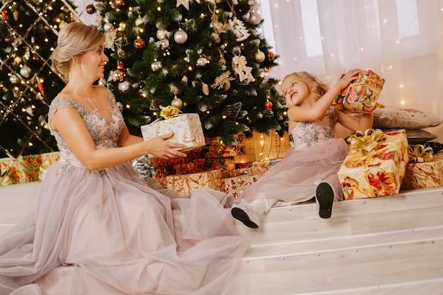クリスマスのコンセプト。クリスマスの部屋で幸せな母と小さな娘。プレゼントをあげる