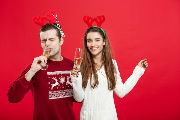 クリスマスのコンセプト-シャンパンでクリスマスを祝うセーターの幸せな若いカップル。