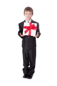 クリスマスのコンセプト白い背景で隔離のギフトボックスとビジネススーツの小さな男の子