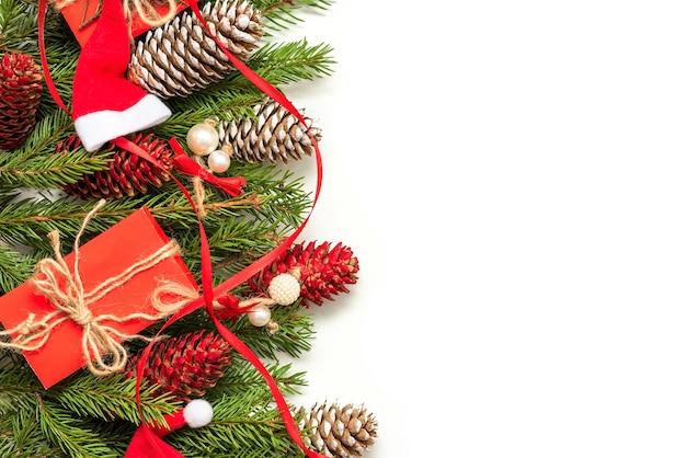 孤立した背景にモミの枝と円錐形で作られた装飾のクリスマスの概念。