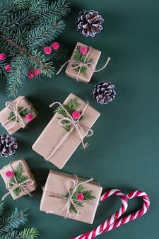 クリスマスコンセプトビンテージベージュクラフトペーパーと自然な装飾のパッキングギフト。モミと赤いベリーの枝。トップビューフラットレイアウト