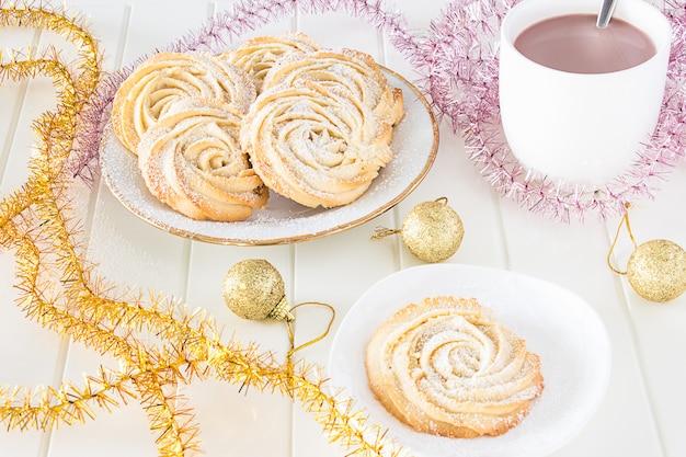 Рождественское понятие. круглое песочное печенье формы розочки с глазурью и чашка горячего шоколада. винтажная белая тарелка. разноцветная мишура. белый фон деревянный.