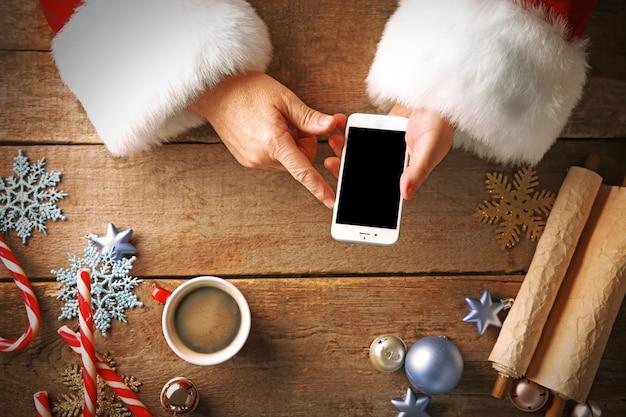 Рождественское понятие. санта берет смартфон в руки над деревянным столом крупным планом