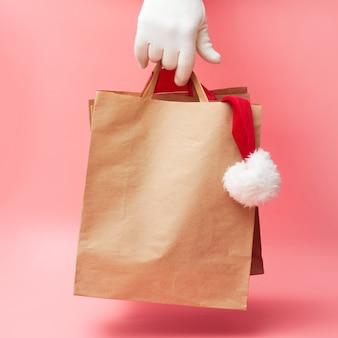 Рождественская концепция, два бумажных пакета в руке, скидки на одежду и аксессуары, на розовом фоне