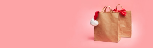 Christmas concept, two paper bags with christmas hat, on pink background, banner, copy space, mock up