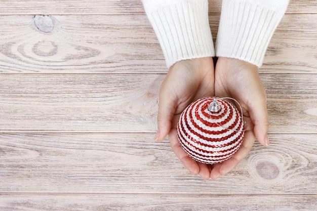 손과 흰색 공-크리스마스 트리 장난감 크리스마스 개념. 여성의 손에 흰색 라운드 크리스마스 공입니다.