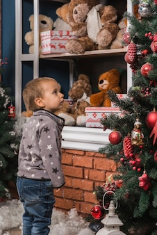 Christmas concept with kid looking at christmas tree