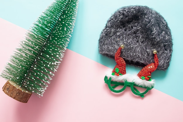 Christmas concept with ornaments and party accessory on pink and green background