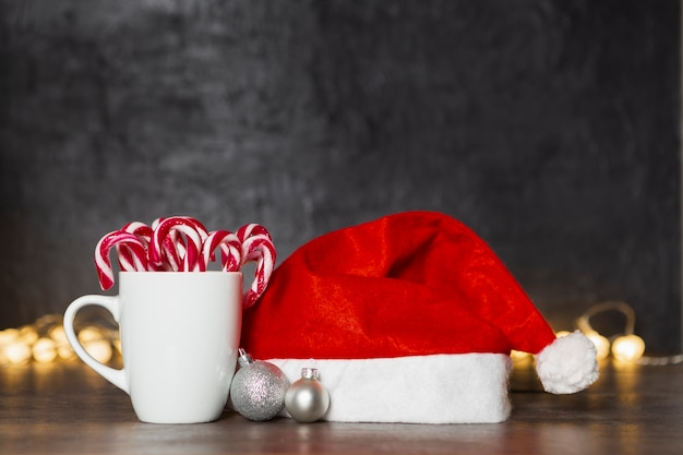 Christmas concept with santa's hat and mug with candy