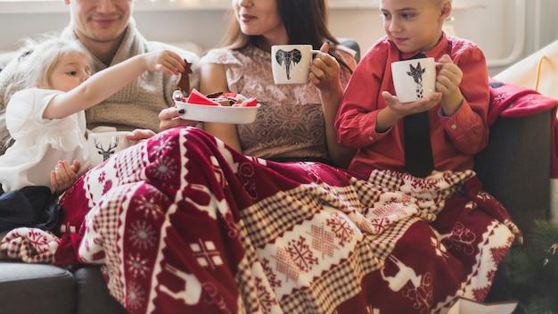 Concetto di natale con la giovane famiglia bere il tè