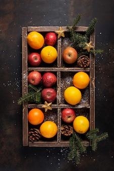 Christmas concept. wooden box with orange, apple and pine cone with christmas decoration. top down view