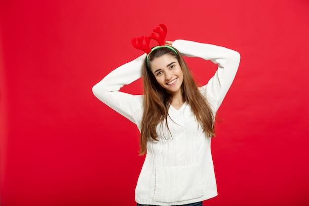 Концепция рождества - молодая привлекательная кавказская леди носит ободок для волос северного оленя, празднуя в день рождества.
