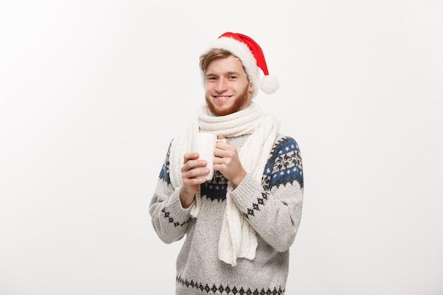 Концепция рождества - молодой человек бороды в свитере и шляпе santa держа горячую кофейную чашку изолированный на белизне с космосом экземпляра.