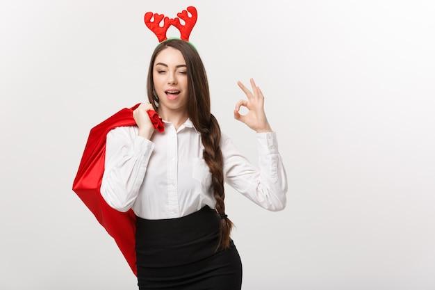 크리스마스 개념-확인 서명을주는 산타 빨간 가방을 들고 크리스마스 테마에서 젊은 아름 다운 비즈니스 여자.