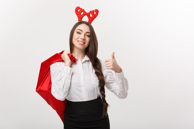 크리스마스 컨셉-엄지 손가락을 포기하는 산타 빨간 가방을 들고 크리스마스 테마에 젊은 아름 다운 비즈니스 여자.