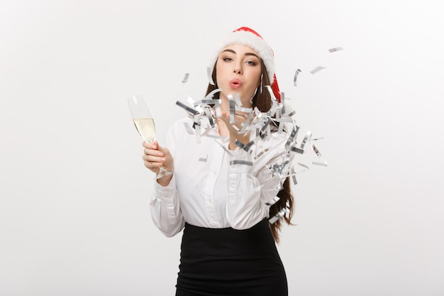 Christmas concept - young business woman holding champagne and blowing confetti.