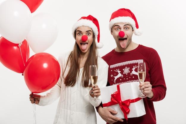 Концепция рождества - молодая кавказская пара держит подарки, шампанское и воздушный шар, делая смешное лицо на рождество.
