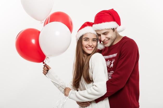 クリスマスのコンセプト-風船を持っている若いガールフレンドは、クリスマスに驚きをしている彼女のボーイフレンドと抱き合って遊んでいます。