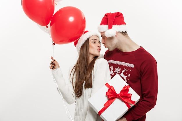 Концепция рождества - молодая девушка, держащая воздушный шар, обнимается и играет со своим парнем, делая сюрприз на рождество.