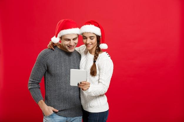 クリスマスのコンセプト-若いハンサムで美しいカップルは、クリスマスの日にタブレットで遊ぶのを楽しんでいます。
