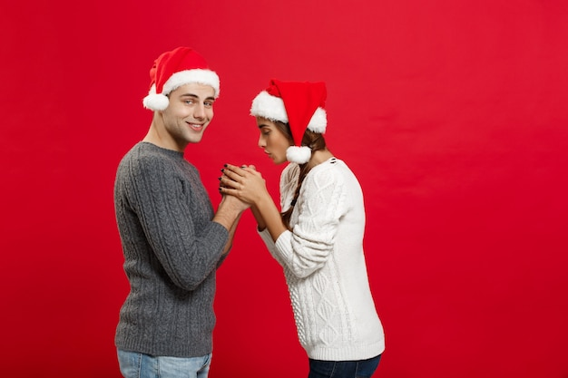 Christmas concept - young stylish couple holding hand each other in winter.