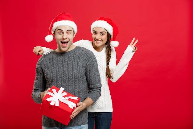 クリスマスのコンセプト-手で男の目を覆い、驚きの大きな贈り物を与える若い女性。赤い壁に隔離。