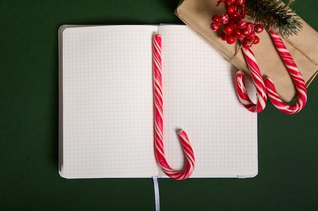クリスマスのコンセプト。ヒイラギとキャンディケインが付いたクラフトラッピングギフトペーパーの美しいシンプルなプレゼント、メモ帳の中央にある甘い縞模様のロリポップ、コピースペースのある空白の空のページ