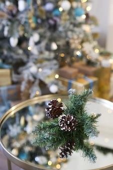 Рождественский конус крупным планом на фоне елки боке и гирлянды