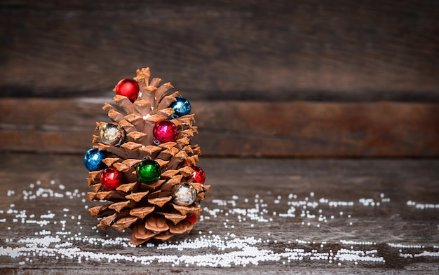 Christmas cone decorated with christmas ornament on dark wooden background