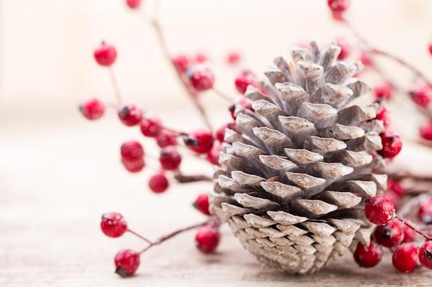 ボケ味の背景に赤い果実とクリスマスコーン