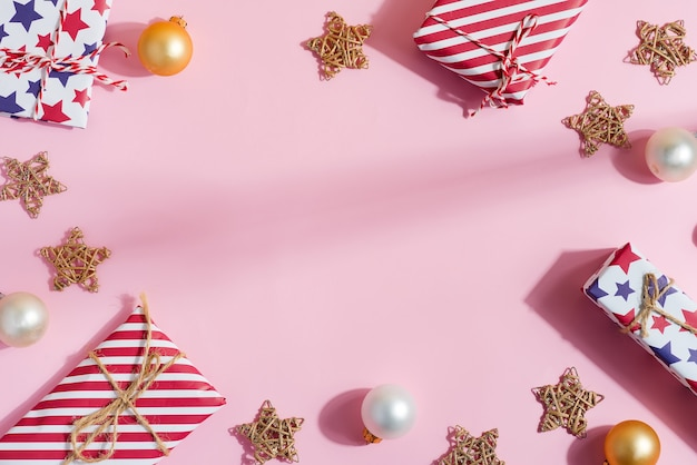 Christmas congratulation frame of colorful gift boxes, decoration stars and balls toys on pastel pink