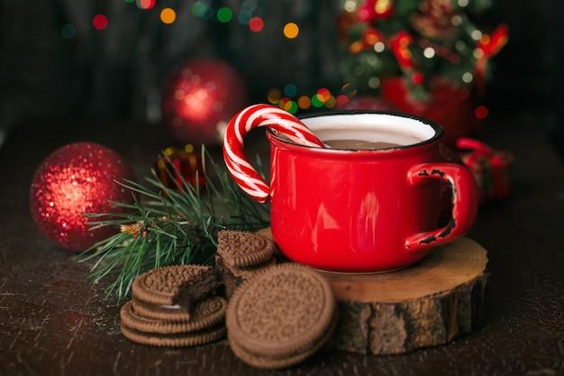 크리스마스 콘텐츠, 코코아가 있는 빨간 머그, 롤리팝, 나무 스탠드, 초콜릿 쿠키, 가문비나무 가지, 크리스마스 트리, 빨간 공, 조명, 어두운 배경
