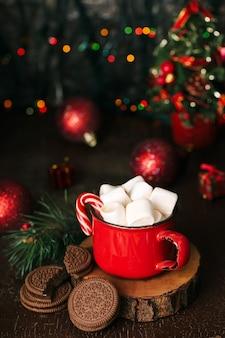 크리스마스 콘텐츠, 코코아가 있는 빨간 머그, 마시멜로, 롤리팝, 나무 스탠드, 초콜릿 쿠키, 가문비나무 가지, 빨간 공, 조명, 크리스마스 트리, 어두운 배경