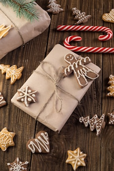Christmas cookie and candy on wood, food top view. gifts with craft paer.