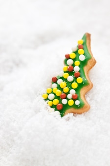 Christmas cookie, glazed christmas tree shape on a snow, closeup, selective focus