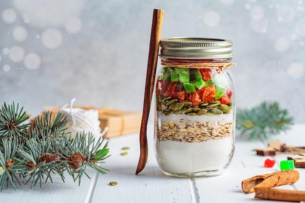크리스마스 쿠키 믹스 항아리. 항아리, 흰색 배경에서 크리스마스 쿠키 요리를위한 건조 재료. 크리스마스 음식 개념입니다.