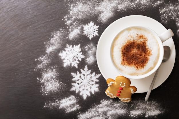 어두운 배경에 크리스마스 쿠키와 카푸치노 한 잔, 위쪽 전망