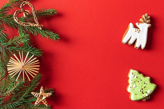 Рождественское печенье и украшенные еловые ветки на красном фоне