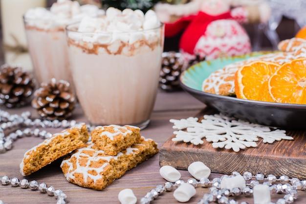 クリスマスクッキーとクリスマスデコレーションとテーブルの上のグラスにマシュマロとホットココア Premium写真