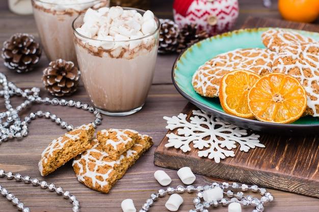クリスマスクッキーとクリスマスデコレーションとテーブルの上のグラスにマシュマロとホットココア