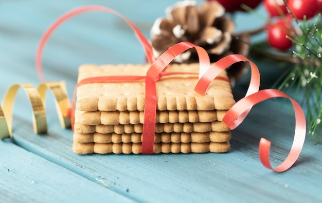Christmas cookies cinnamon, pine cones, cedar branches with golden lights on wooden table.