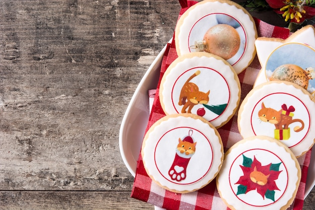 Christmas cookies decorated with christmas graphics on wooden table