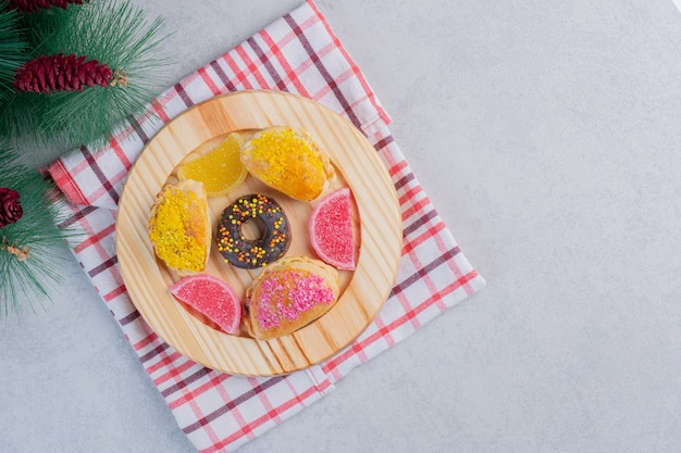 Christmas cookies, donut and marmalades on dark plate.