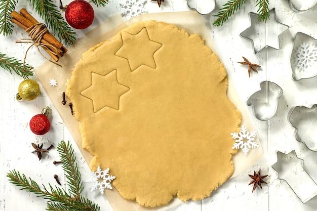 クリスマスクッキーホームキッチンテーブルのジンジャーブレッドスパイス小麦粉のジンジャー生地上面図